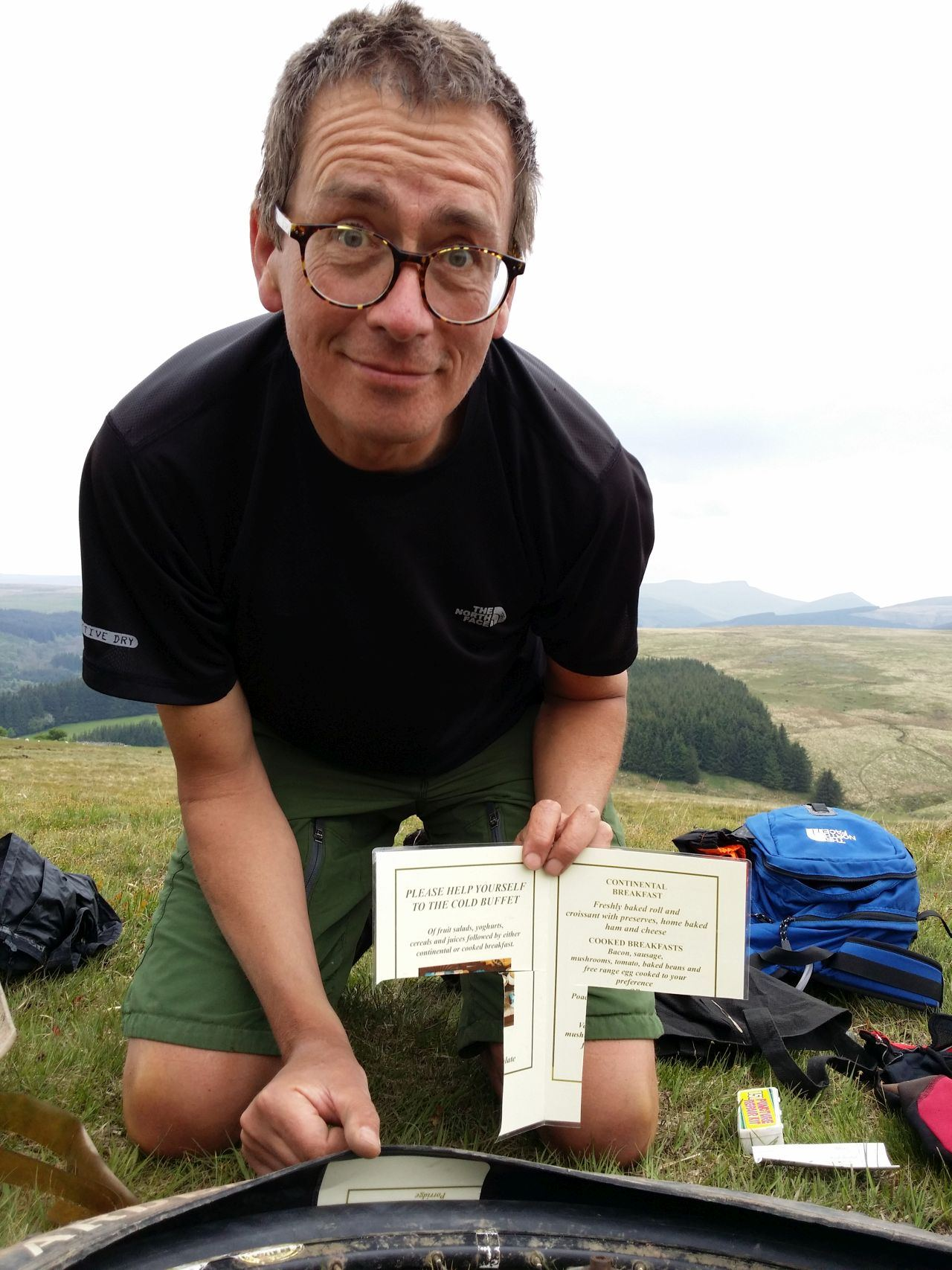 Day 7 - Trailside repair novelty ... having run out of tyre boots improvising On slopes of Cefn y Ystrad with laminated menu after Paul`s tyre splits again! © Paul Bonwick