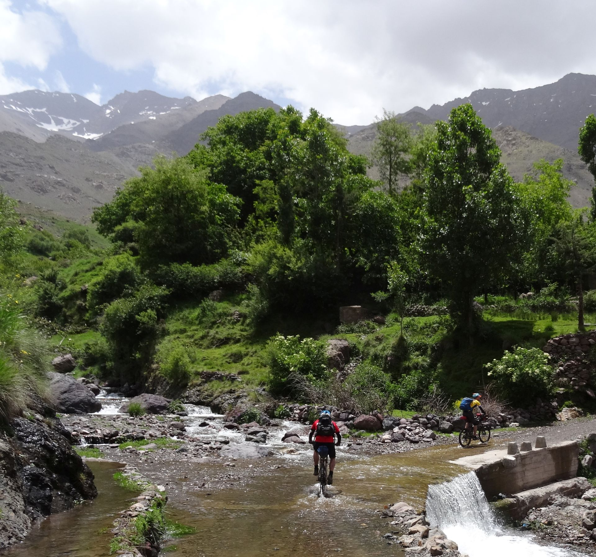 Day 8 - Splish Splash Splosh, & nearly Bish Bash Bosh! Wheel dip in the Assif Imenane river, leaving Tizi-n-Tacheddirt, en route to Imlil, before our final day of riding, tomorrow. Bou Iguenouane (12,736 ft) on left, Jbel Aksoual (12,828 ft) right - form part of a 10-mile ridge traverse for another time! © Steve Woodward
