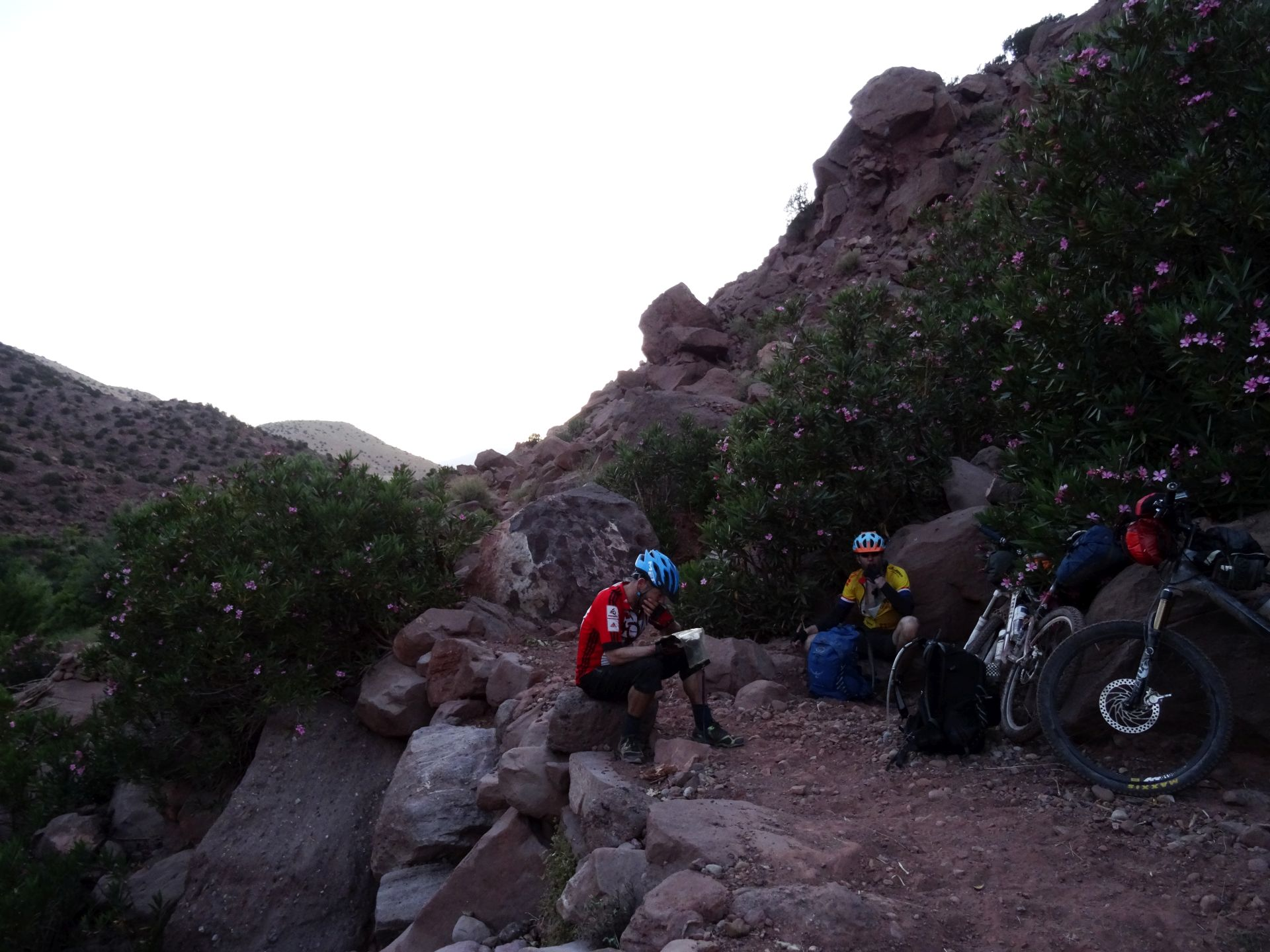 Day 6 - Getting dark, but not there yet! Food & nav break in the dust. Hauling bikes over boulders as big as us is now the norm :( Slow, slow going. On the trail toward Tighza © Steve Woodward