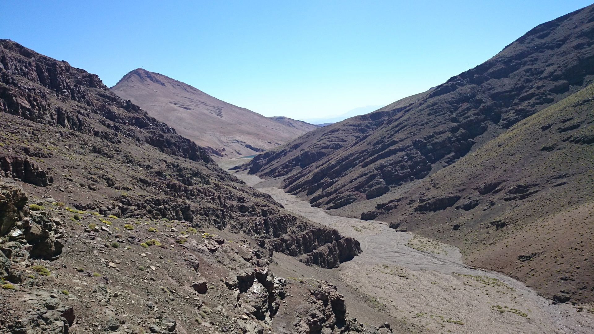Day 6 - The moon AKA the descent from the Tizi-n-Tamadla pass & the dried-up river bed across which we need to ride (boulders!) Looking west, with lake Tamda in the distance, & flanks of Jbel-n-Anghomar on the right.  © Shaun Grey