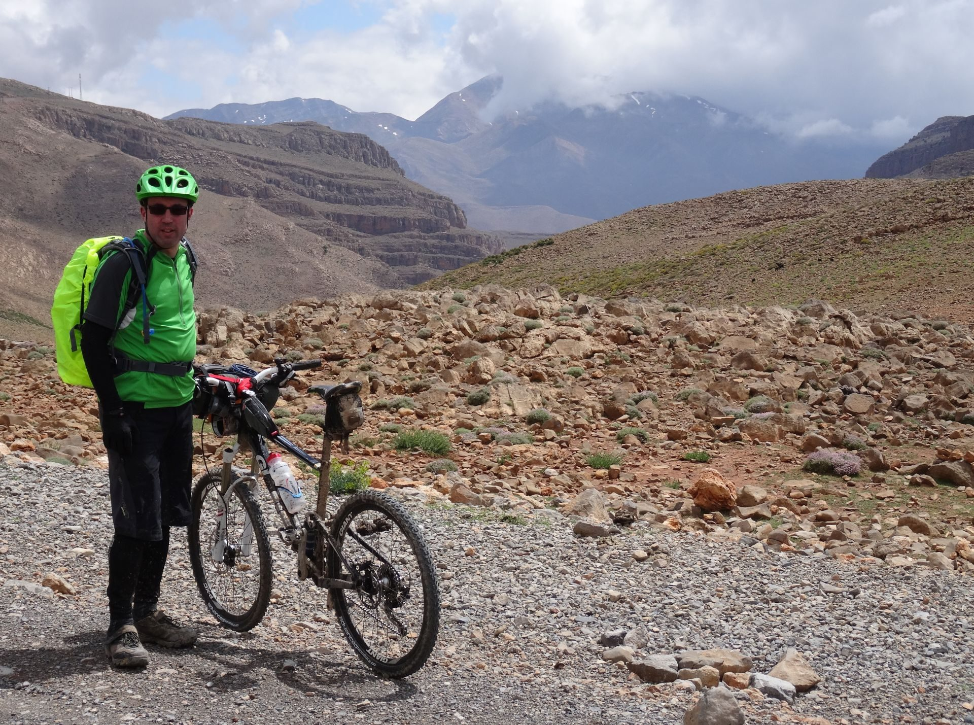 Day 1 - Mountain (Bike) Man, Steve. On the climb up the Tizi-n-Ouanergui pass (8,238 ft), before dropping into Anergui. Jbel Leqroun in cloud, on horizon. © Steve Woodward