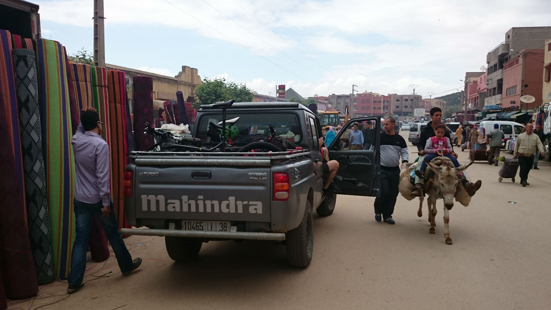 Transfer Day A - Our driver, Abdel, prepares to negotiate carpet movement (left) while child takes test for muleteer licence (right). Lunch stop in the market town of El Ksiba, during our transfer by pick-up from Marrakesh  to Imilchil, where we`ll start the ride. © Shaun Grey