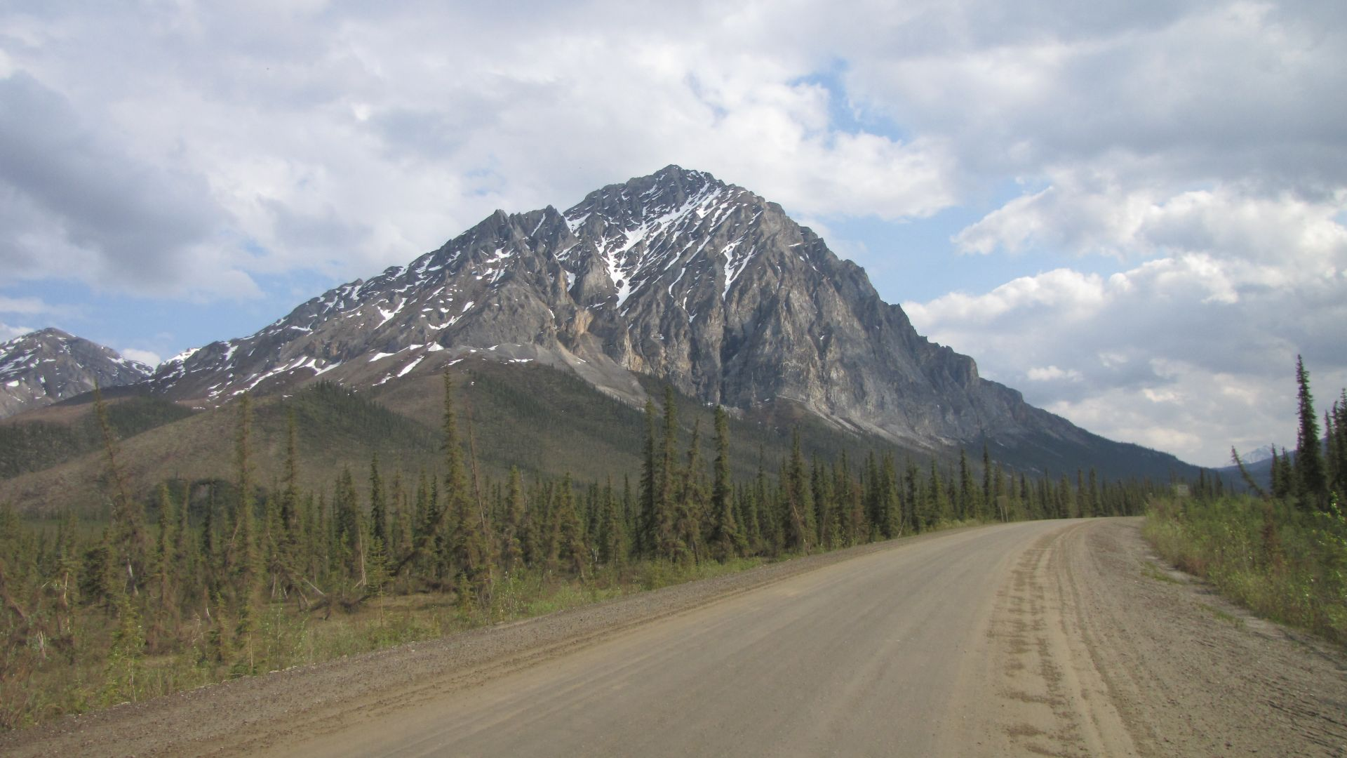 """Sukakpak Mountain, northern Alaska, USA, at the end of a very, very long day of gravel-riding over the snow-bound Brooks Range, on the way to the tiny truckstop at Coldfoot, after a week of wild camping in bear country. Taken during """"Part 1"""" of my 7-month solo ride in 2009 from the Arctic Ocean coast to Mexico, later following the length of the Rocky Mountains"""