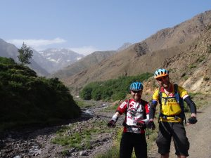 "Day 9 - It`s been a long two weeks on the road! We`re on our bikes right? Right? ;) ""Riding"" beside the Oued Rheraya river, on the way back to Marrakesh. The mountain on the left is the highest peak in North Africa, Jbel Toubkal (13,671 ft). Crikey. © Steve Woodward"