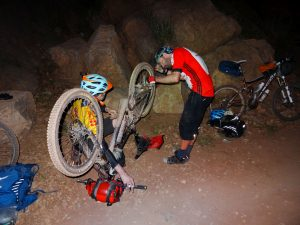 "Day 6 - Repairing a snapped-off rear derailleur in the dark, after nearly 14 hours on the bikes. ""Can we fix it? ... Yes we can!"". Shaun AKA Bob the Builder master-mechanic does the final checks ... Somewhere between Tighza & Anguelz! © Steve Woodward"